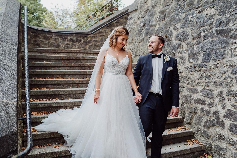 Brautpaar geht steinerne Treppe hinunter