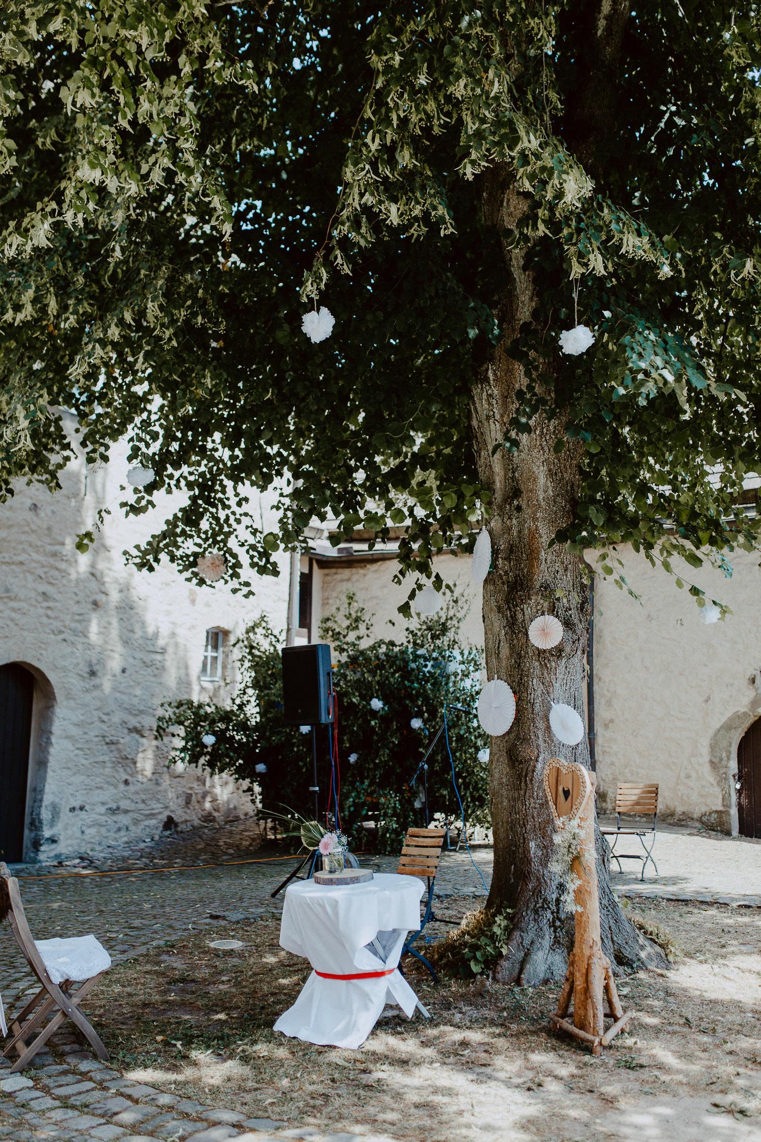 Burghof mit Baum und Hochzeitsstühlen auf Burg Sternberg