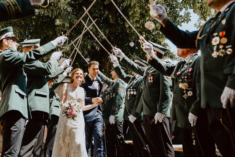 Brautpaar geht durch spalier stehende Schützen
