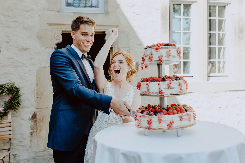 Braut jubelt beim Hochzeitstorte anschneiden