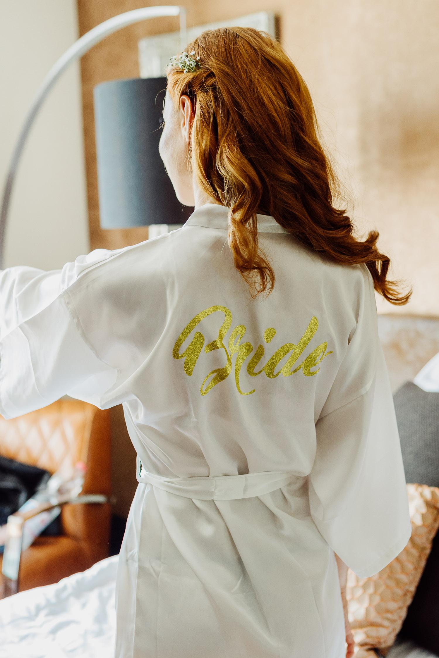 Braut trägt Bademantel mit Schriftzug