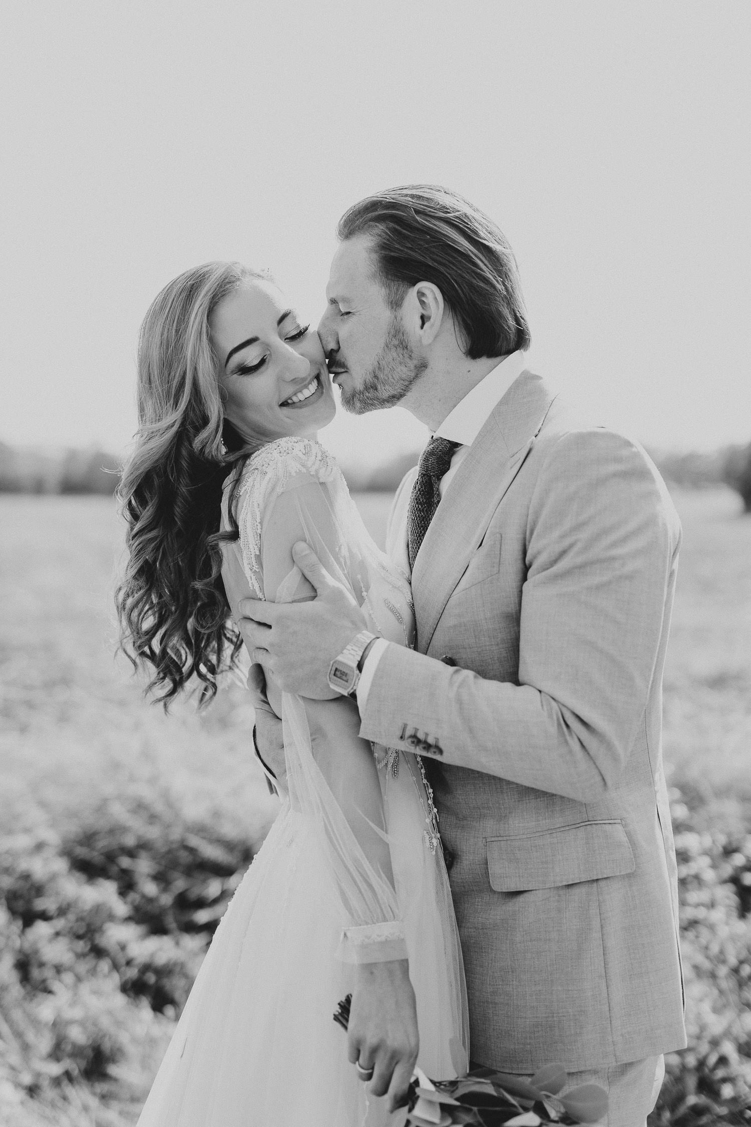 Bräutigam küßt Braut auf die Wange in schwarz weiß
