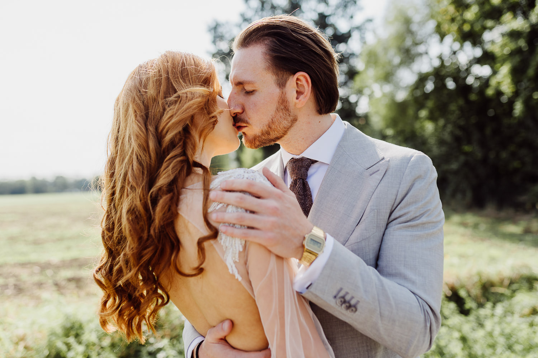 Brautpaar küßt sich auf dem Feld