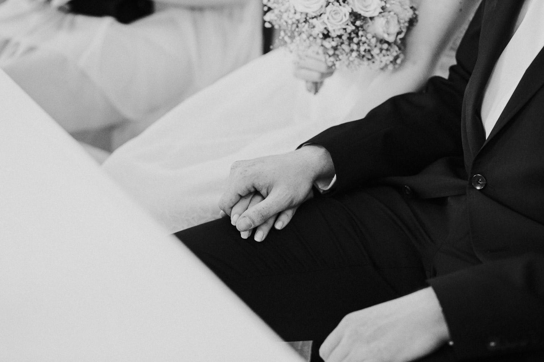 Brautpaar hält sich die Hand bei standesamtlicher Trauung