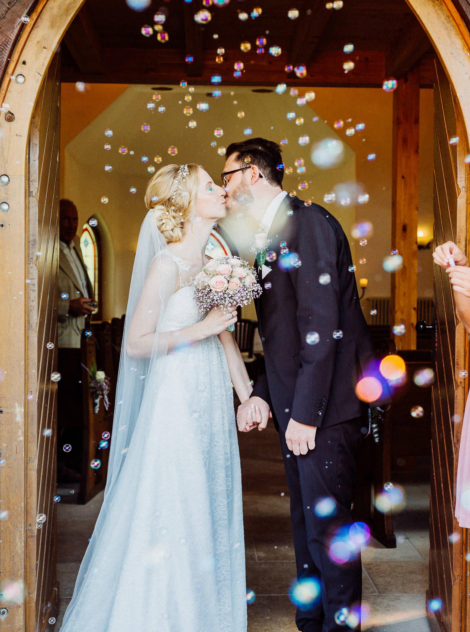 Brautpaar küßt sich beim Auszug nach Trauung im Fachwerkdorf Liebhart