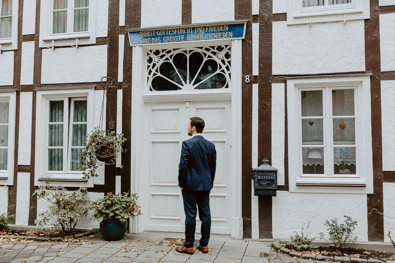Bräutigam wartet vor Fachwerkhaus auf den First Look