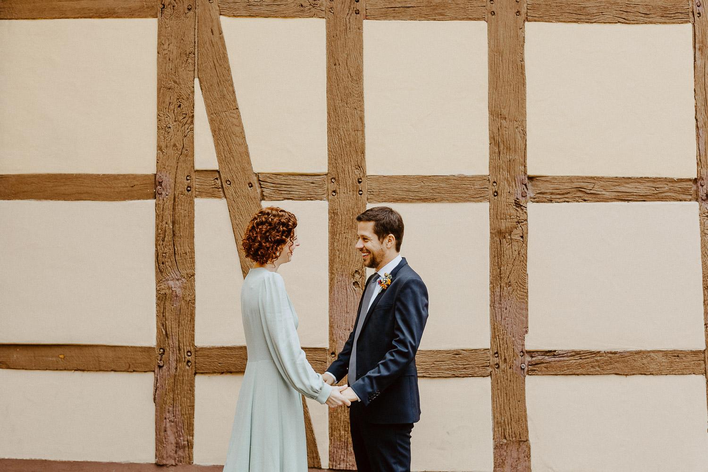 Braut und Bräutigam halten sich an den Händen vor dem Standesamt