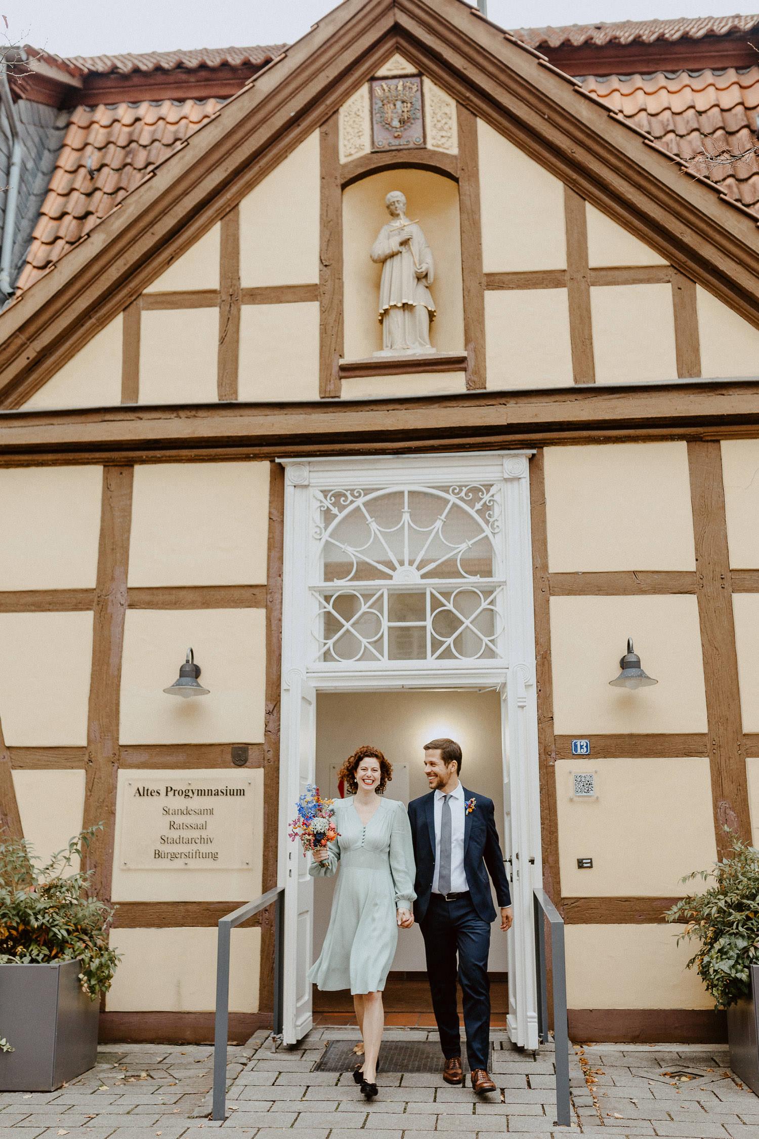 Brautpaar komm Hand in Hand aus dem Standesamt Rietberg
