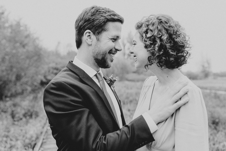 Bräutigam lacht mit Braut bei Hochzeit im Gartenschaupark Rietberg