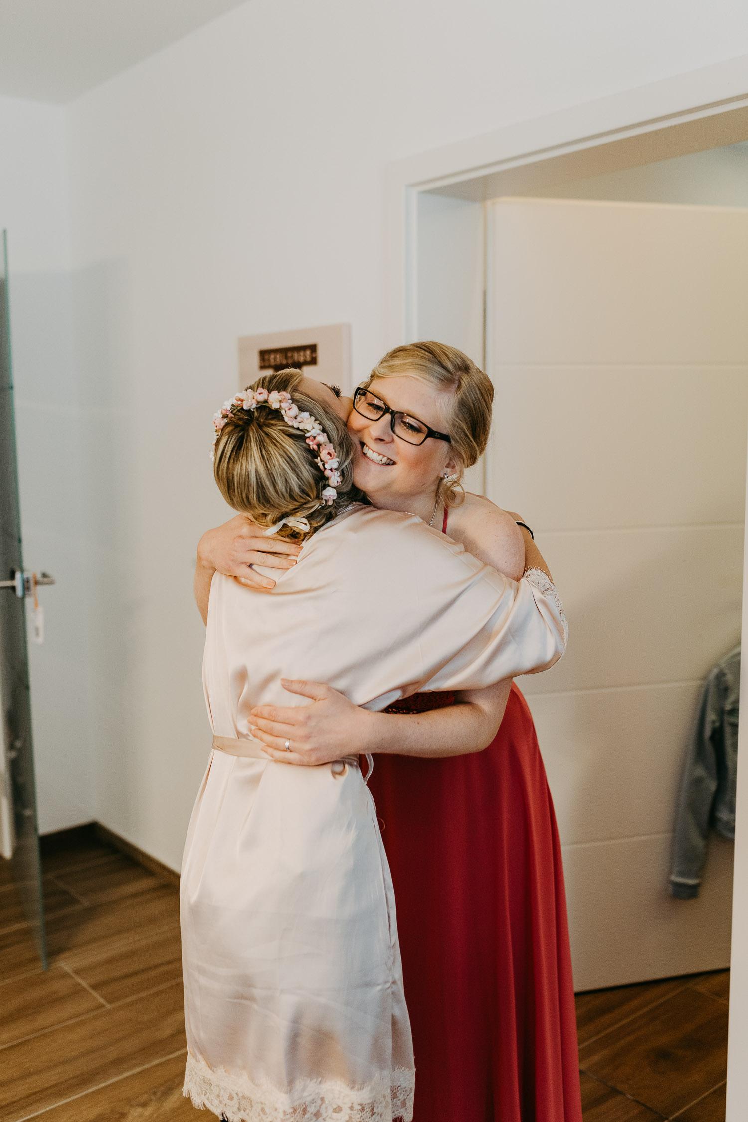 Braut und Trauzeugin umarmen sich