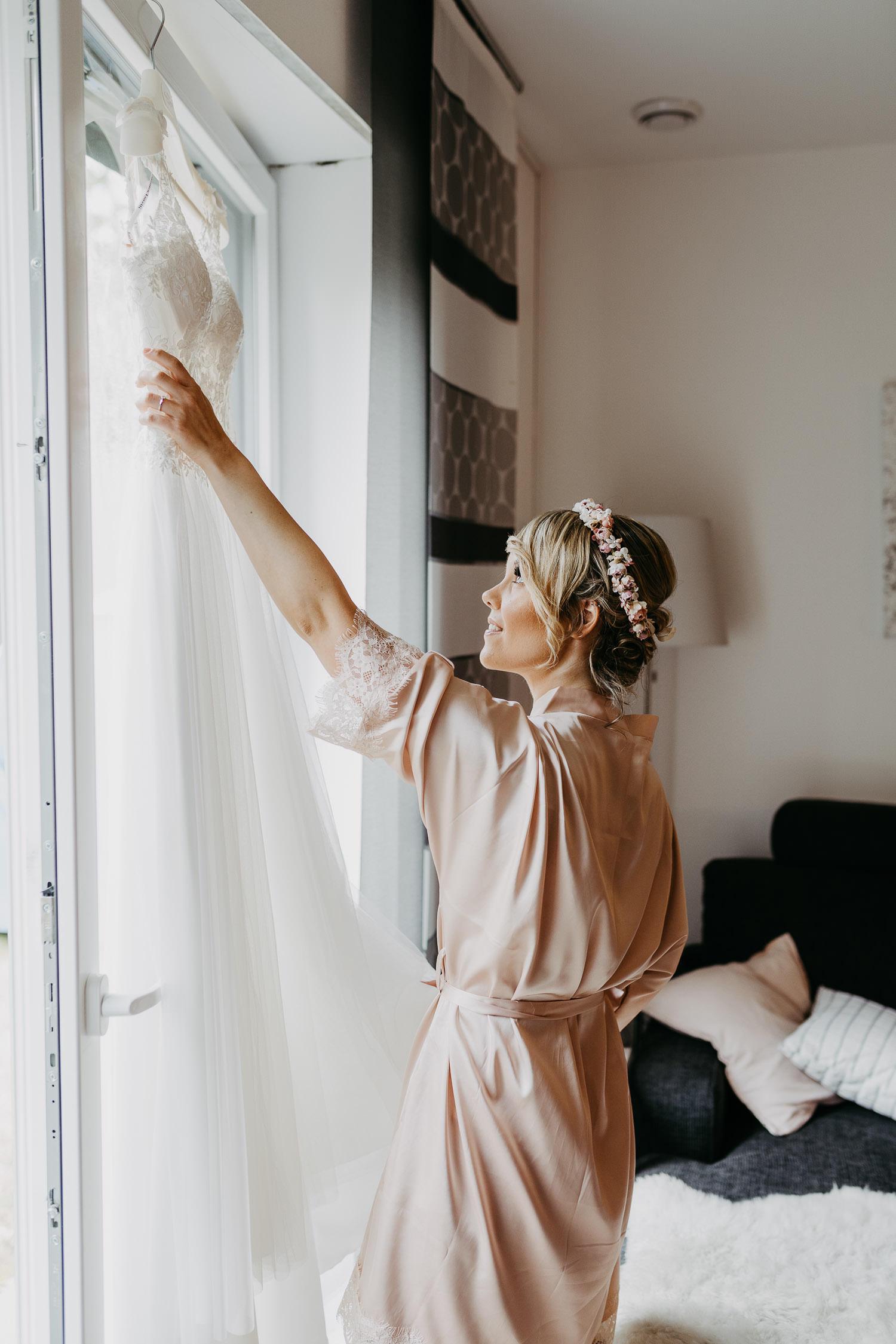 Braut schaut sich Brautkleid an