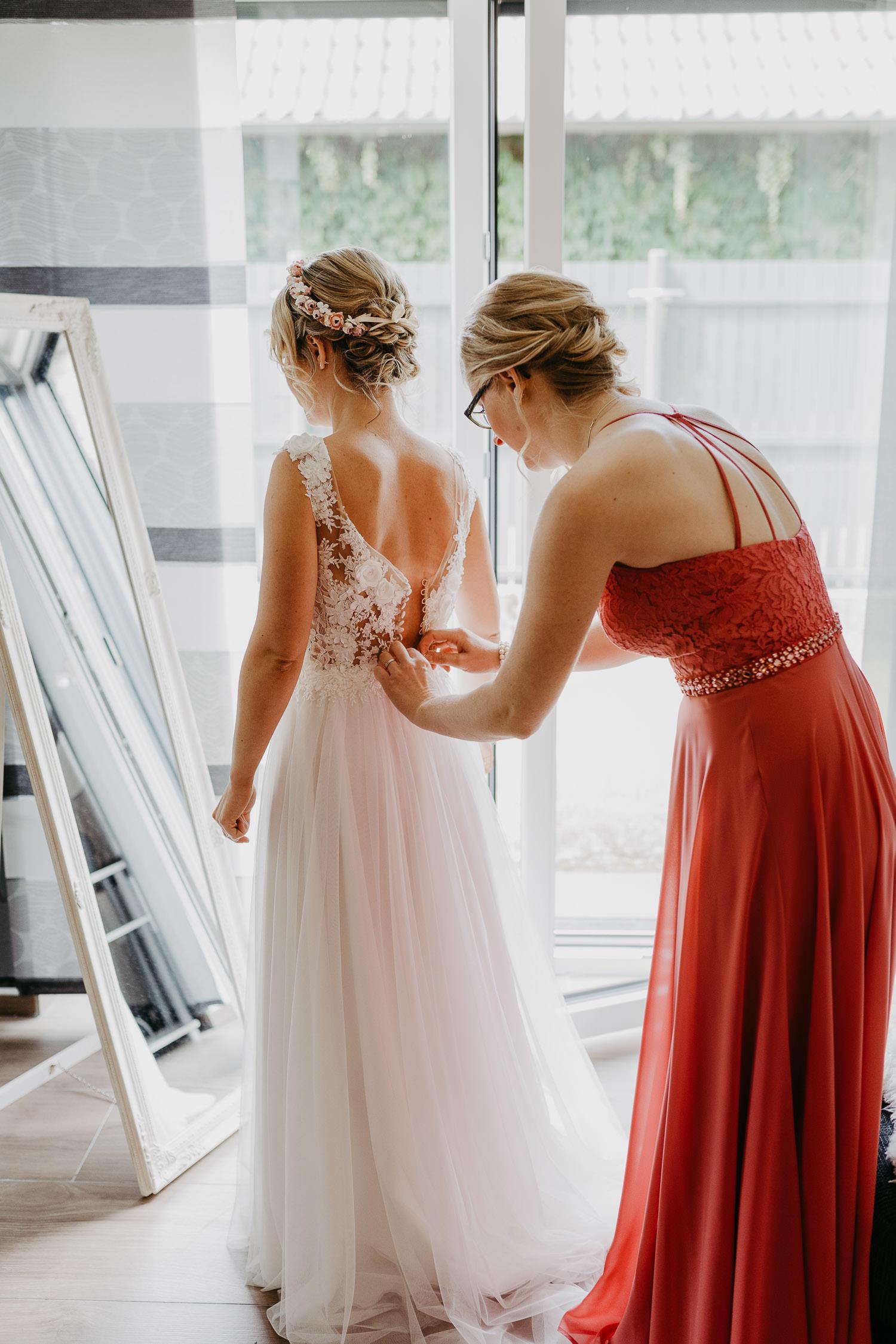 Freundin schließt Knöpfe an Brautkleid
