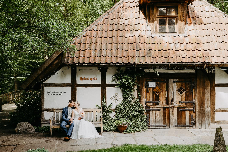 Brautpaar sitzt auf der Bank vor Hirtenkapelle im gastlichen Dorf Delbrück