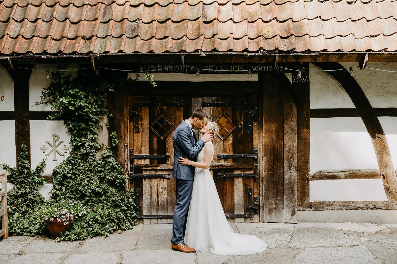 Brautpaar küsst sich vor Hirtenkapelle im gastlichen Dorf Delbrück