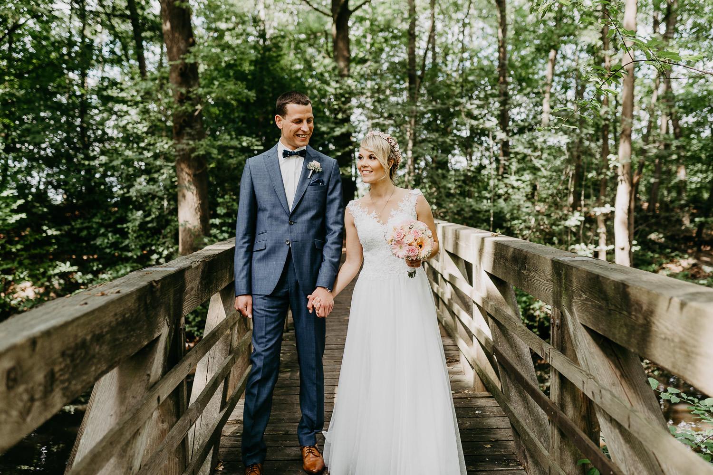 Brautpaar geht über Brücke im gastlichen Dorf Delbrück