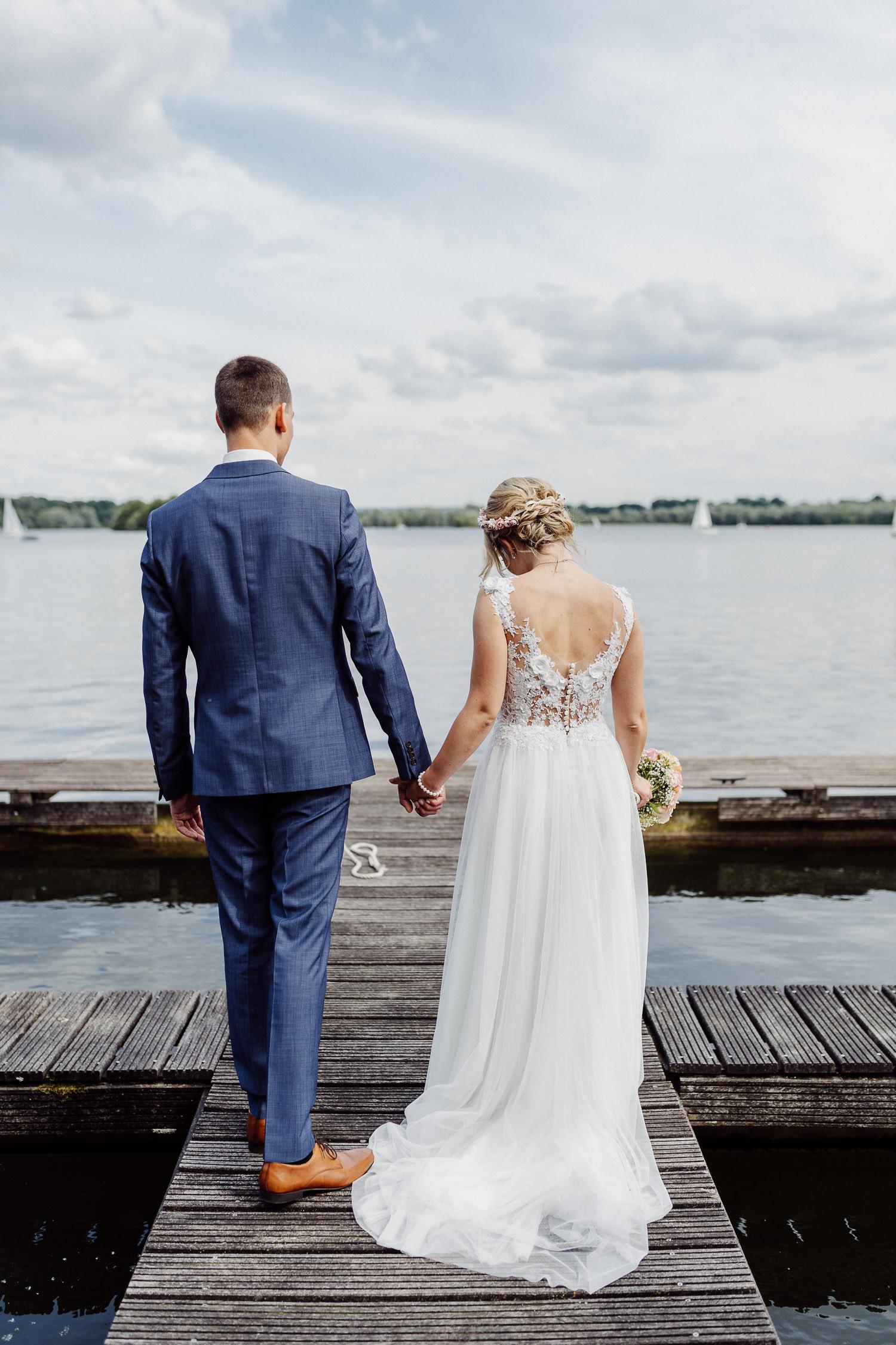 Brautpaar geht über Bootssteeg am Lippesee
