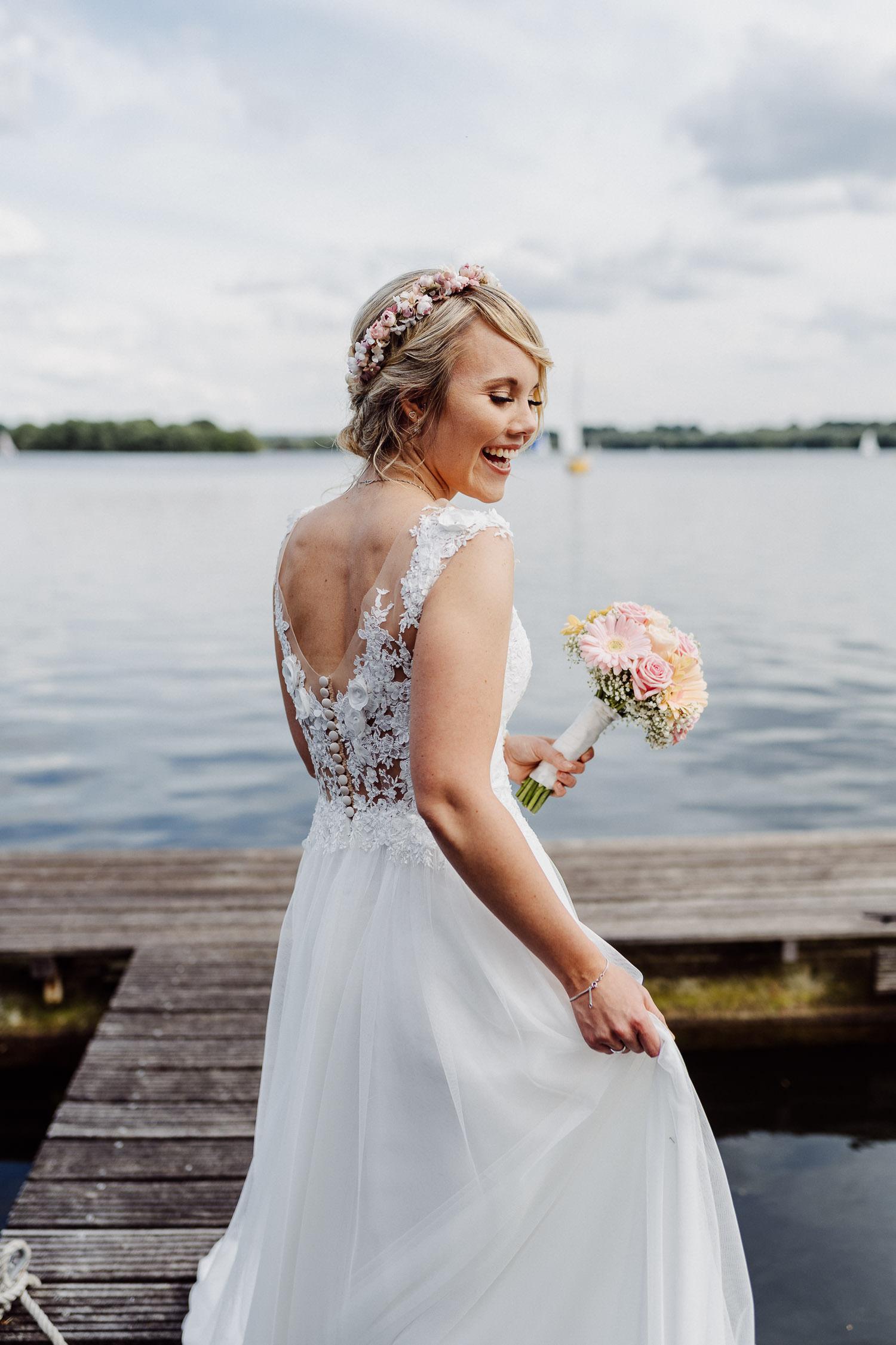 Braut im Brautkleid geht über Bootssteg