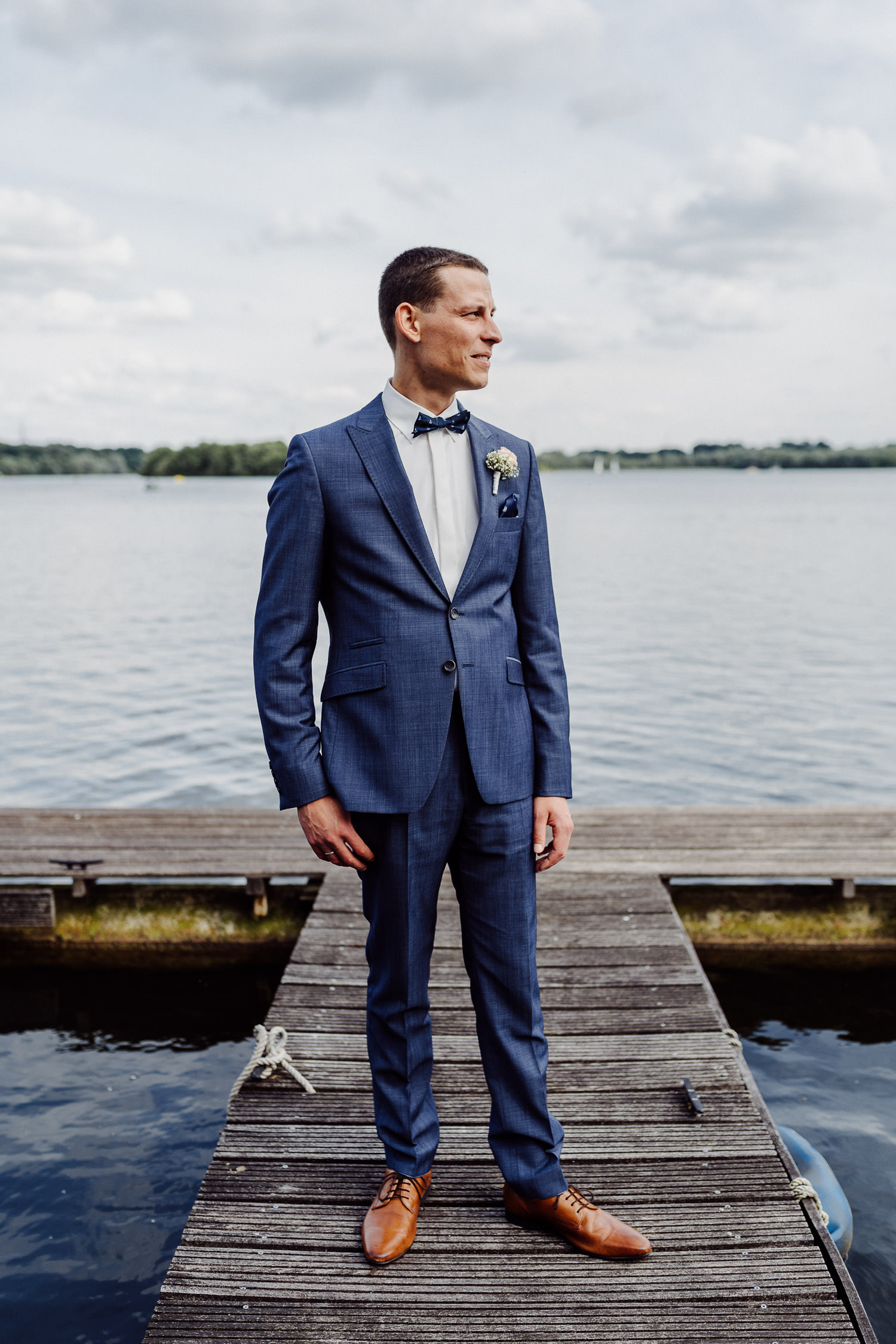 Bräutigam auf Bootssteg am Lippesee in blauem Anzug