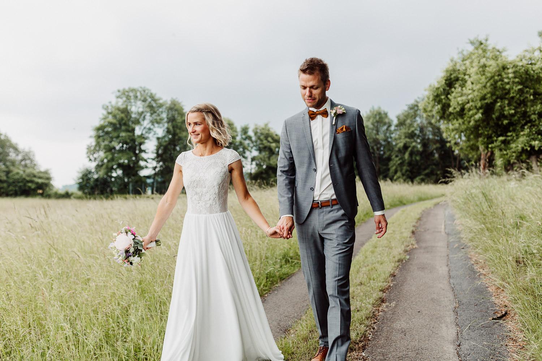 Brautpaar geht an Wiese entlang