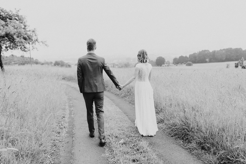 Brautpaar geht Weg entlang mit Blick auf Bielefeld