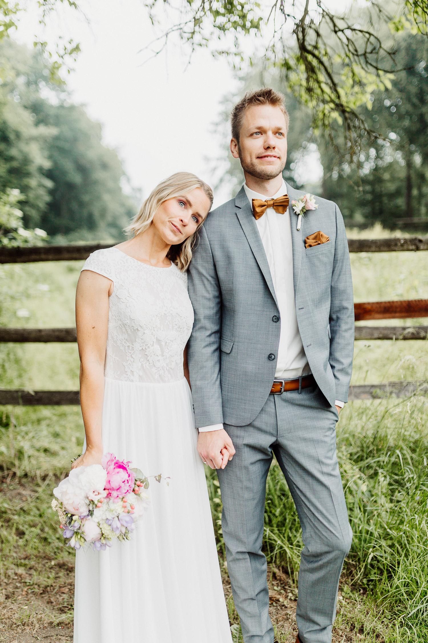 Brautpaar Hand in Hand vor Wiese