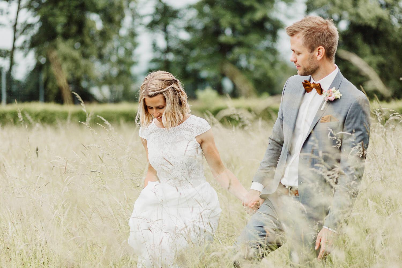 Brautpaar schreitet durch Weizenfeld