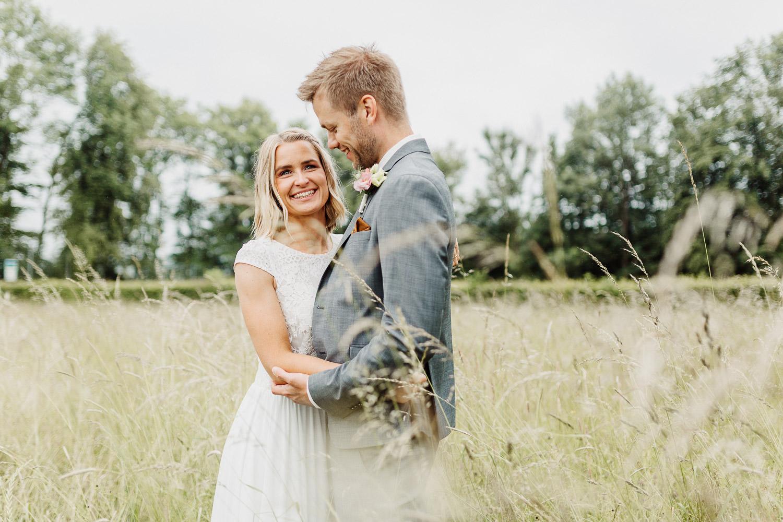 Brautpaar steht in Weizenfeld