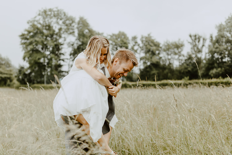 Bräutigam trägt Braut durch ein Feld