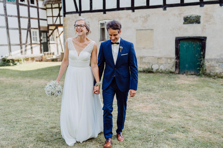 Brautpaar geht Hand in Hand über den Hof von Laer
