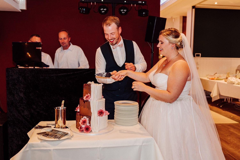 Brautpaar schneidet Hochzeitstorte an im Lind am See