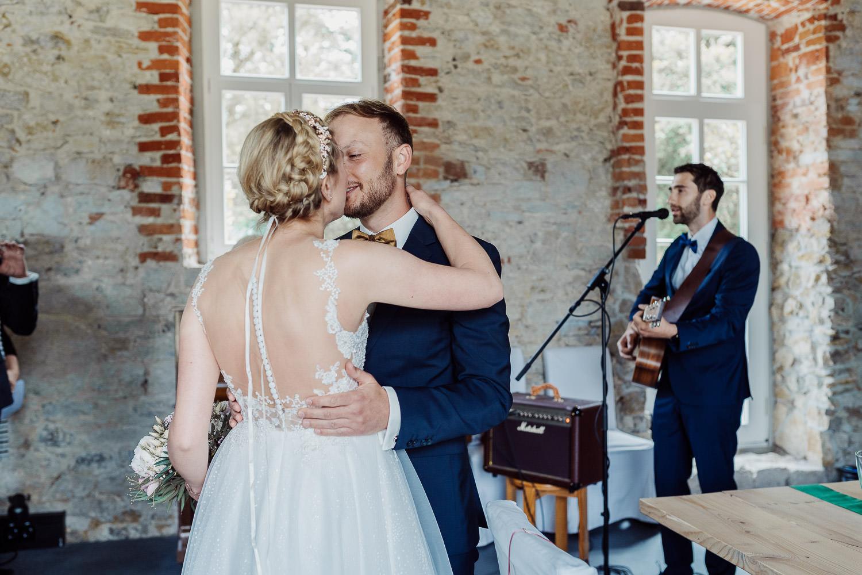 Braut küsst Bräutigam vor der Hochzeit
