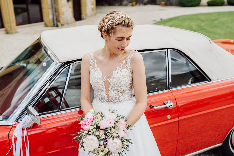 Braut vor rotem Oldtimer bei der Remise Niederbarkhausen