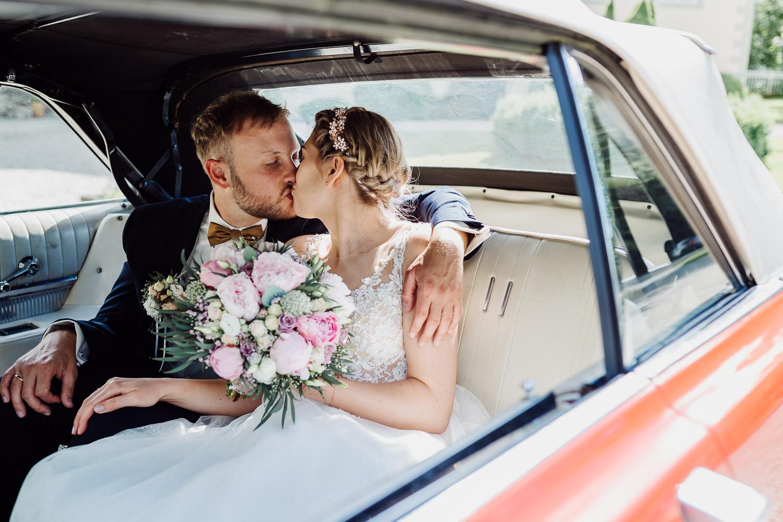 Brautpaar küsst sich in Oldtimer