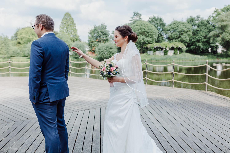 Braut tippt Bräutigam an beim First Look Shooting