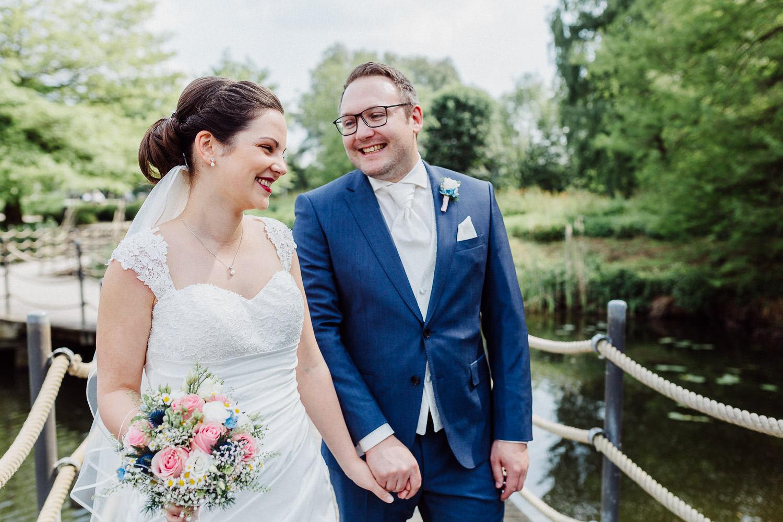 Hochzeitsfotos am Emssee in Rheda Wiedenbrück Brautpaar lacht auf Brücke