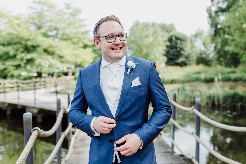 Bräutigam knüpft sich das Jacket zu auf dm Steg über dem Emssee