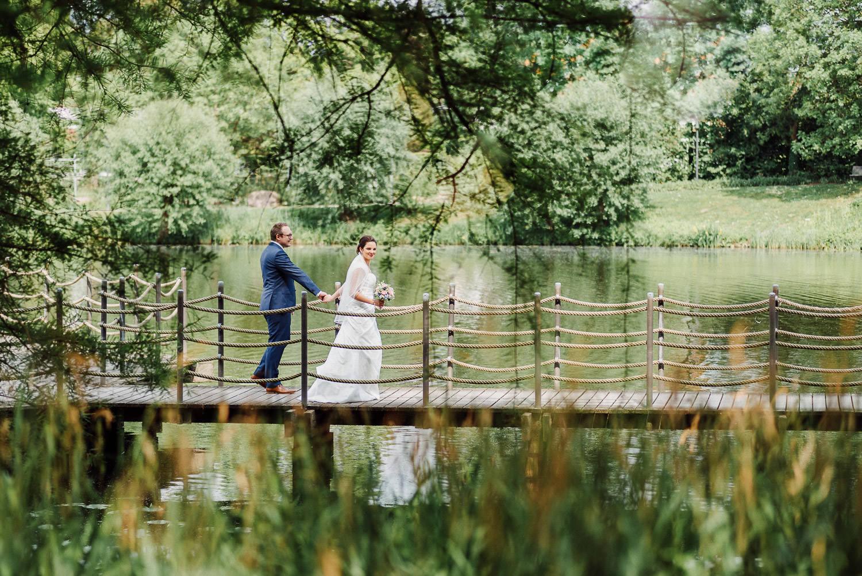 Hochzeitsfotos am Emssee in Rheda Wiedenbrück Brautpaar geht über die Brücke