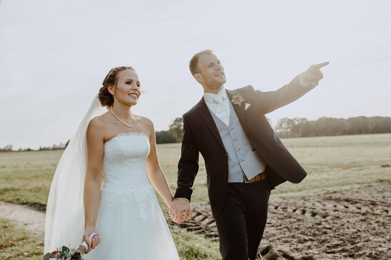 Brautpaar spaziert auf Feldweg