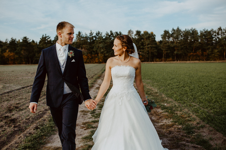 Braut und Bräutigam Hand in Hand auf Feldweg