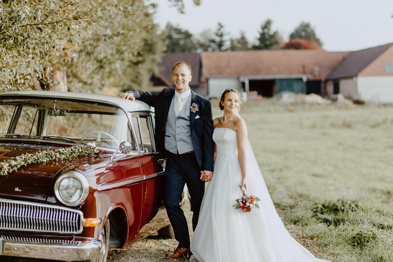 Brautpaar vor rotem Oldtimer nach Oktoberhochzeit