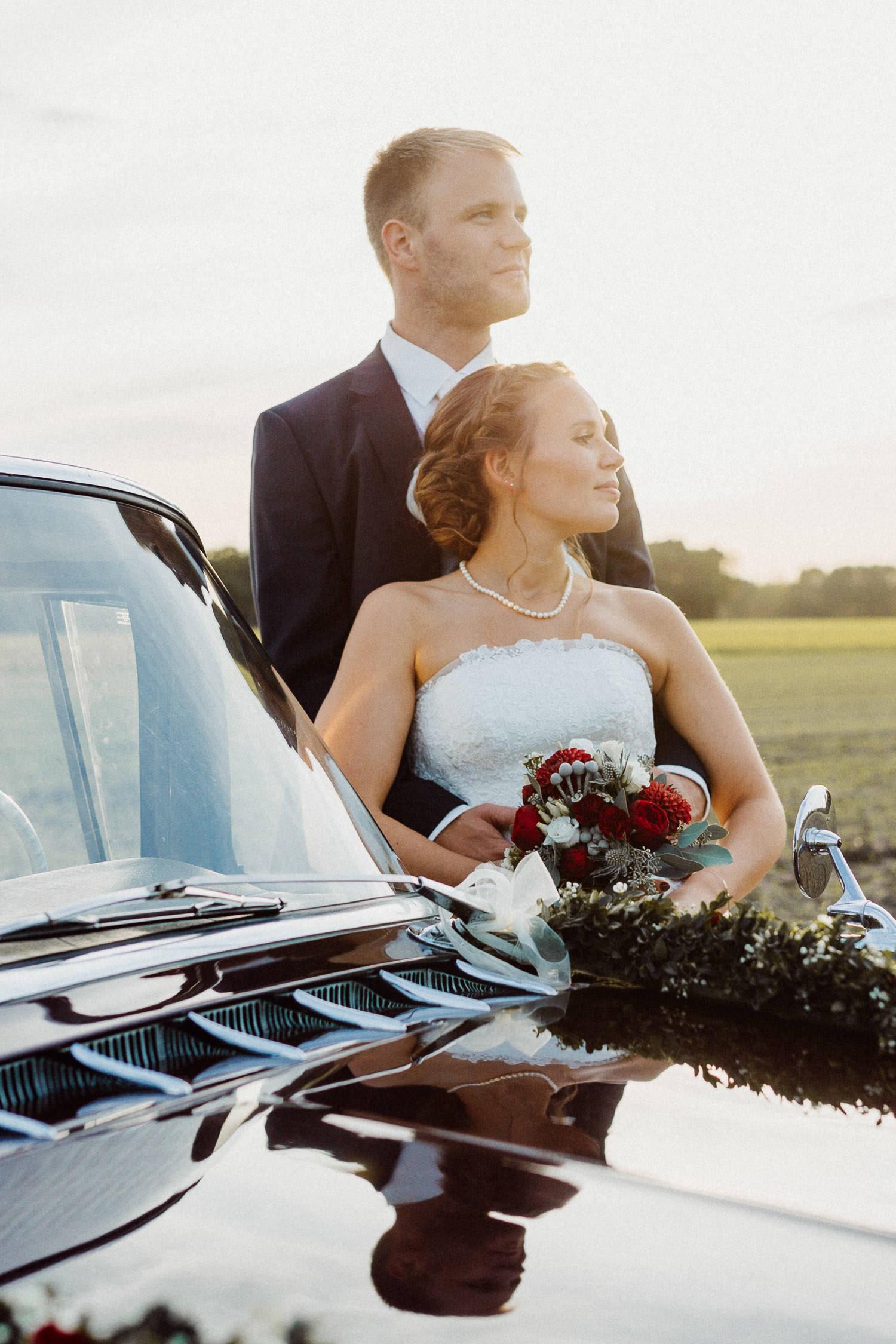 Brautpaar lehnt an Oldtimer