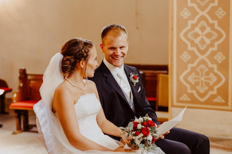 Brautpaar lächelt sich zu in der Kirche während Oktoberhochzeit