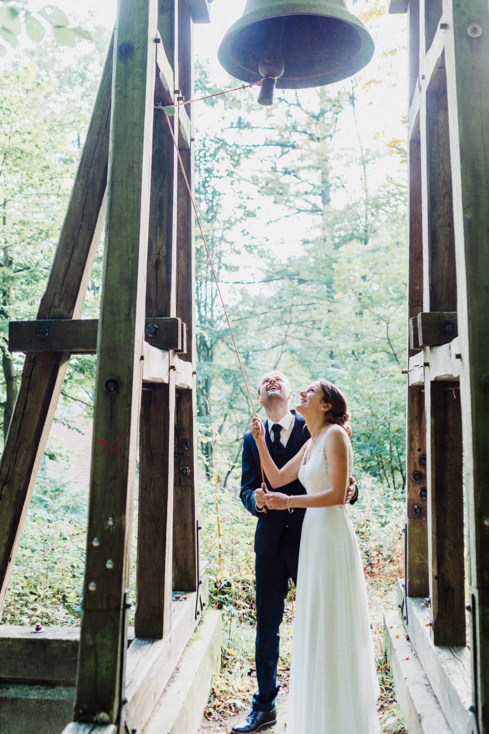Brautpaar läutet die Glocke an open air Kirche Waterböhr
