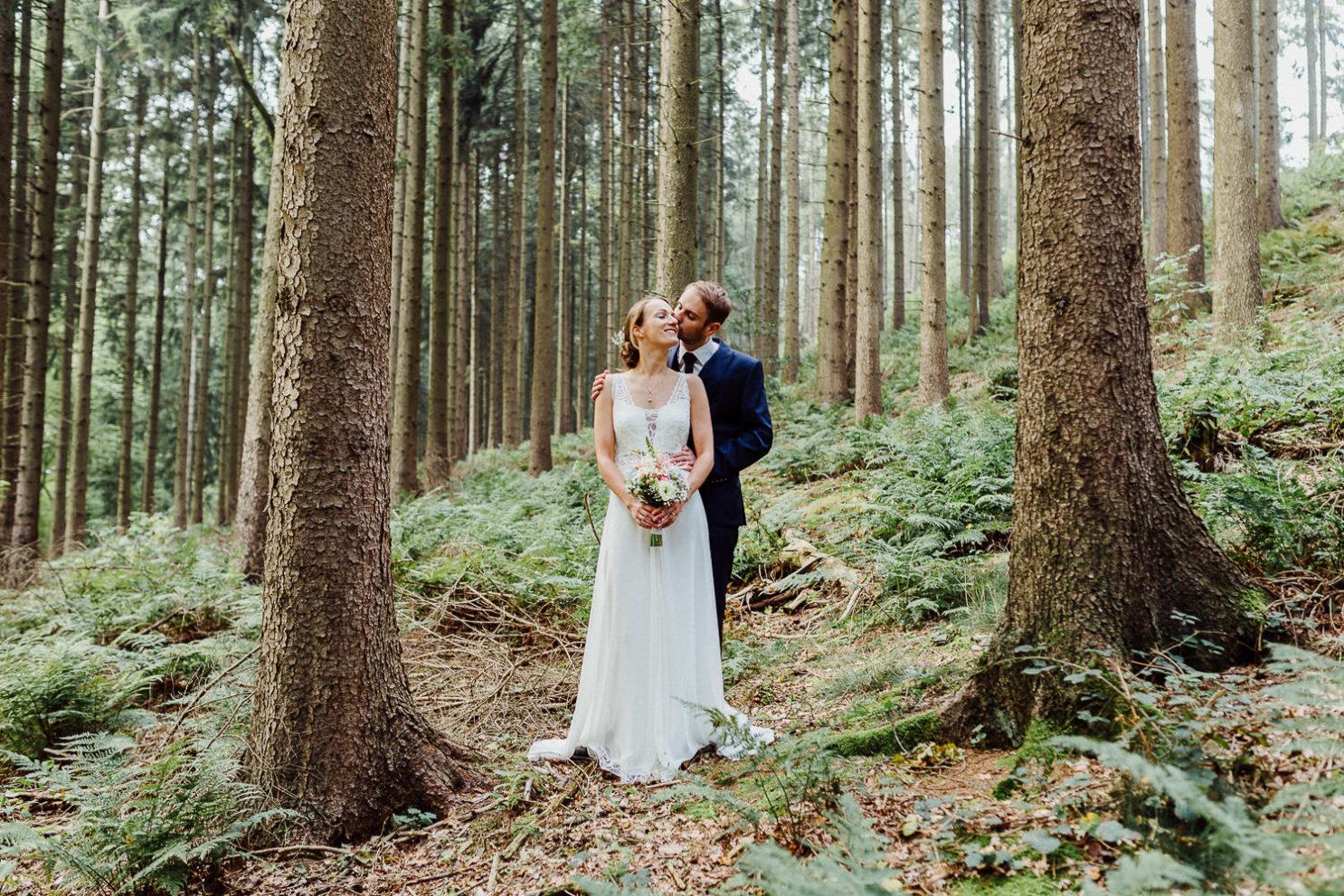 Bräutigam küßt Braut bei Hochzeitsshooting im Wald