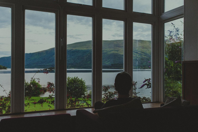 Mann schaut durch Fenster auf Loch Lomond Schottland
