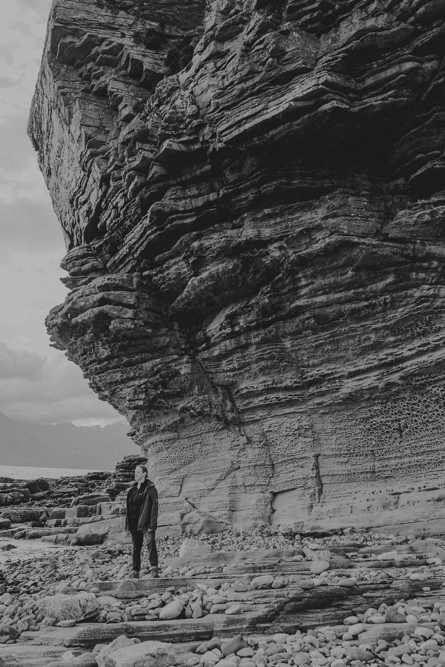 Frau steht vor großem Felsen in Elgol