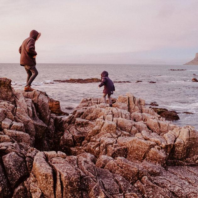 Vater und Sohn klettern auf Steinen in Nordirland