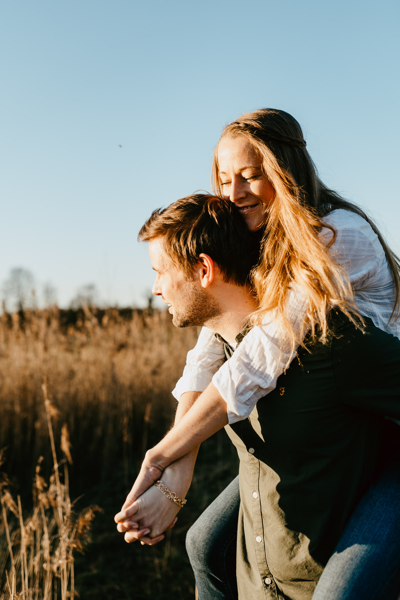 Paarfoto Frau sitzt Huckepack in der Sonne